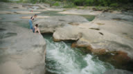 Girl helps sister out of crater and sits on rocky outcrop over roaring river rapids.