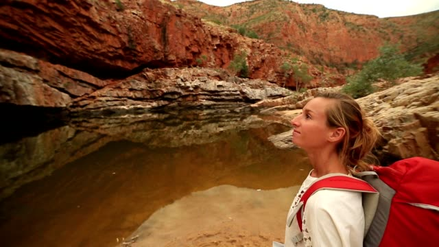 Girl hiking in the outback reads map for directions
