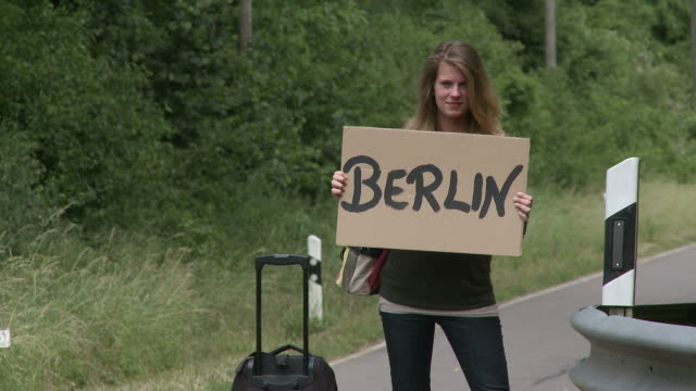 MS Girl hitchhiker standing with sign / Saarburg, Rhineland-Palatinate,  Germany