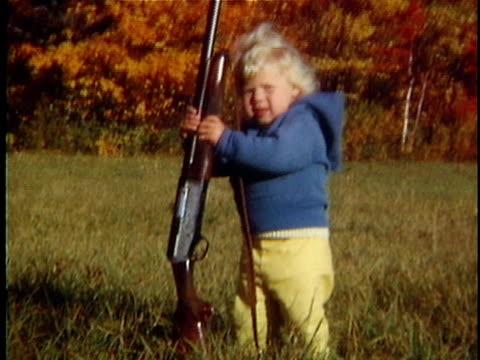 Girl (2-3) holding shot gun in field, Vermont, USA