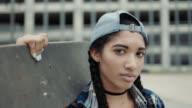 MS SLO MO. Girl holding skateboard turns and looks at camera in skatepark.
