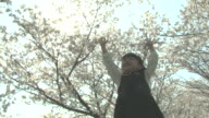 LA Girl holding up arms under cherry tree