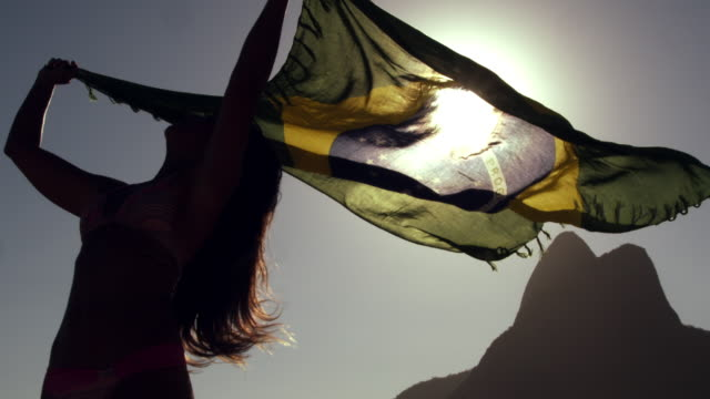 Girl holds Brazilian flag on the wind, by Ipanema Beach
