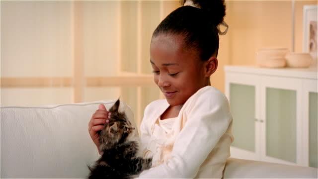CU, ZO, ZI, Girl (6-7) hugging Maine Coon kitten, portrait