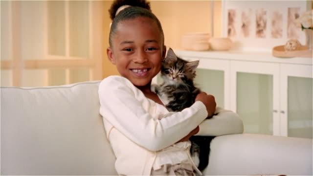 CU, ZI, ZO, Girl (6-7) hugging Maine Coon kitten, portrait