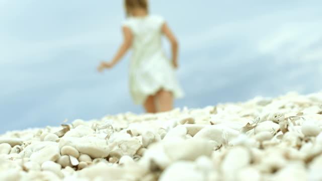 Mädchen in einem Kleid tragen Sie die weiße Kiesel an der Meeresküste