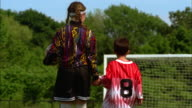 A girl in a soccer uniform holds hands with a boy in an over sized soccer jersey.