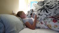 girl in bed using tablet