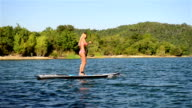 Girl in bikini on stand up paddle board