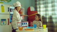 MS Girl (4-5) in chef outfit serves cookies to another girl in play kitchen set / Burbank, California, USA