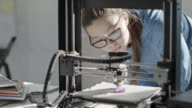 Girl in glasses coding and 3D printing detail