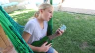 girl in hammock, playing a ukulele