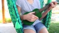 girl in hammock, playing a ukulele