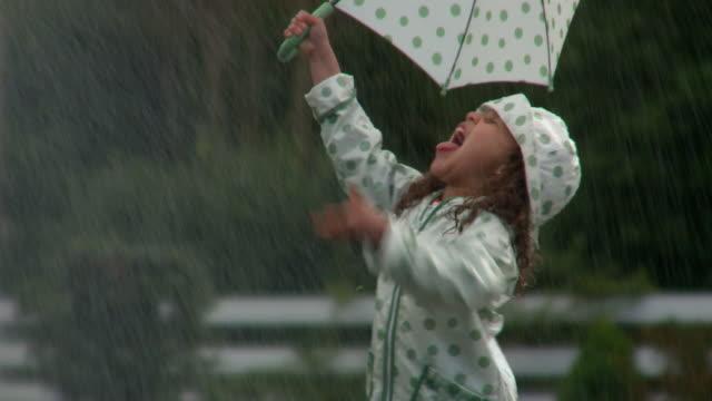 MS Girl in raincoat holding umbrella playing on street during rain / Richmond, Virginia, USA