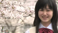 Girl in school uniform smiling by cherry tree