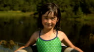 MS PORTRAIT girl in swimsuit standing on edge of pond with an inner tube around her/ Bovina, New York