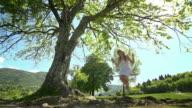 Girl in white dress swinging on rope swing under tree