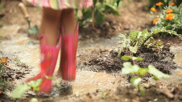 CU TD TU Girl (4-5) jumping in mud in vegetable garden / Richmond, Virginia, USA