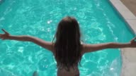 Girl jumping into the water from the front. Back view.