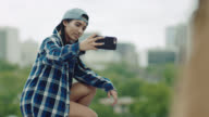 Girl kneels to take selfie on graffiti wall overlooking Austin city skyline.