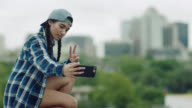 Girl kneels to take selfie on smartphone with downtown Austin in background.