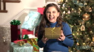 Girl laughing, holding Christmas present