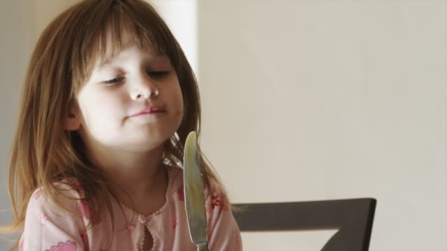 CU Girl (4-5) licking knife in kitchen / Cedar Hills, Utah, USA
