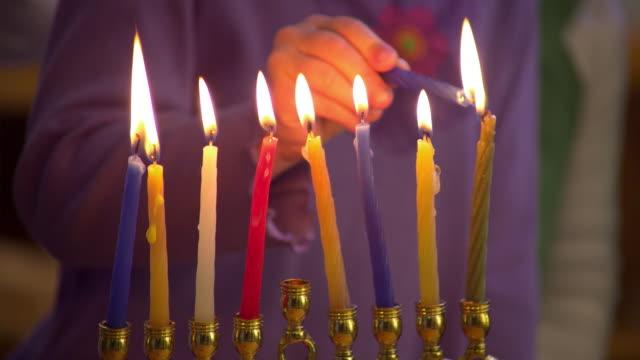 CU TU Girl (6-7) lighting Hanukah candle on menorah, Cambria, California, USA