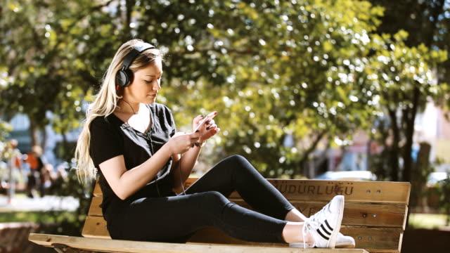 Girl listenin music with phone in public park