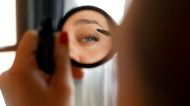 Girl looking at the mirror applying make up