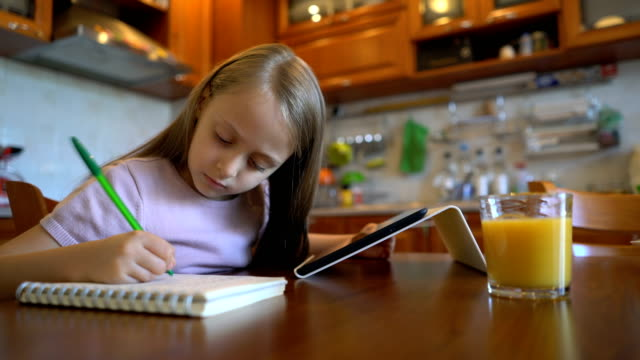 Girl looking at the tablet and handwriting in her journal
