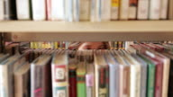 CU Girl looking for books seen through bookshelf / Flagstaff, Arizona, USA