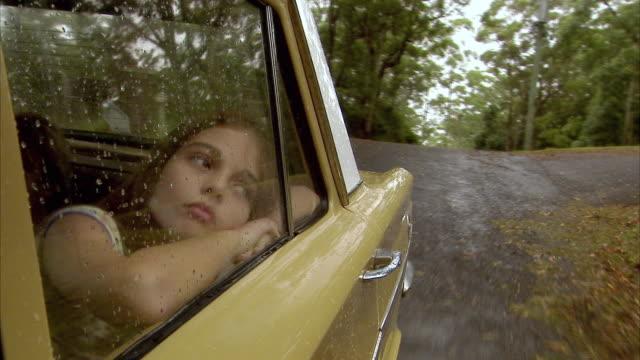 CU, Girl (10-11) looking through car window in rain, Tamborine Mountain, Brisbane, Queensland, Australia