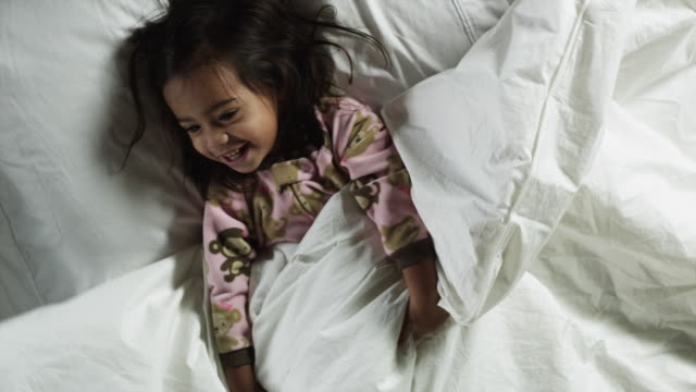 MS Girl (2-3) lying in bed/ Orem, Utah, USA