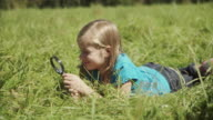 MS Girl (8-9) lying in meadow and looking at grass through magnifying glass / Hampton, New Jersey, USA