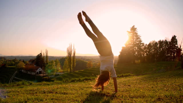 SLO MO Girl makes acrobatic move in meadow