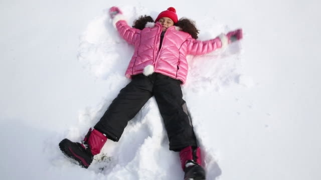 girl making a snow angel