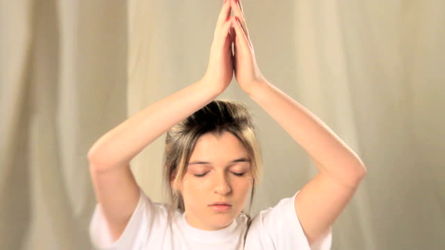 Girl meditating arms above her head.