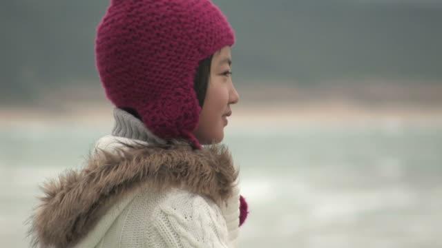 Girl on beach, looking toward camera