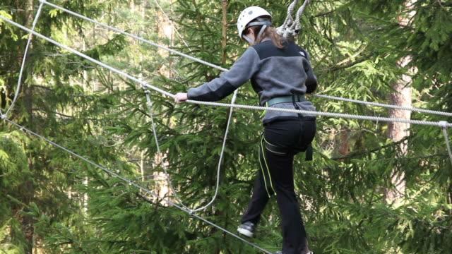 Mädchen auf High Ropes Course in Bäumen