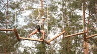 Girl on High Wires Ropes course, with trees (Adventure sports)