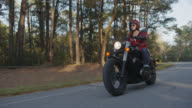 SLO MO. Girl on motorcycle cruises through shadows and sunlight on lonely forest road.
