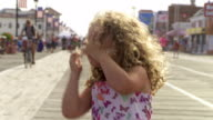 A girl on the boardwalk looks at the camera.  She has rosy cheeks and is chatting with her dad