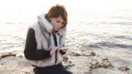 Girl on the coast with phones