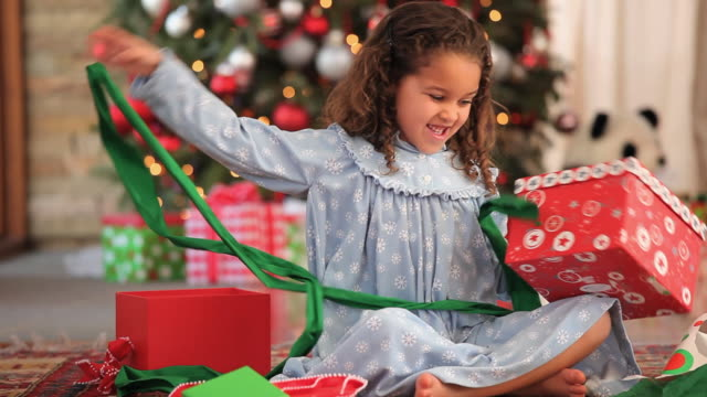 MS TU Girl (4-5) opening present and hugging teddy bear on Christmas morning / Richmond, Virginia, USA