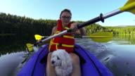 Girl paddling Kayak across a lake with pet dog