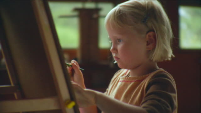 CU Girl painting on easel with paint brush / Vinalhaven, Maine, USA