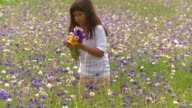 MS PAN Girl (8-9) picking wildflowers on meadow and giving them to mother, Eastville, Virginia, USA