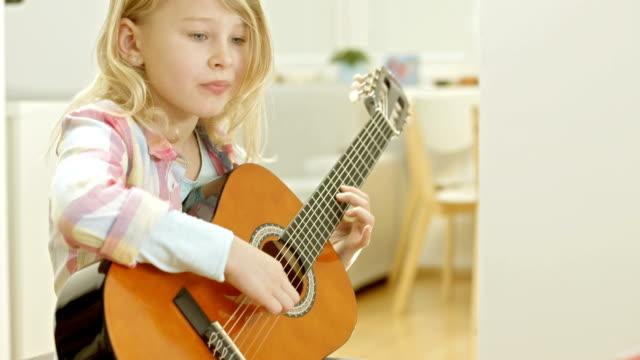 Mädchen spielt die Akustische Gitarre