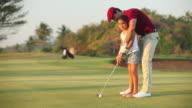 Girl playing golf with her father